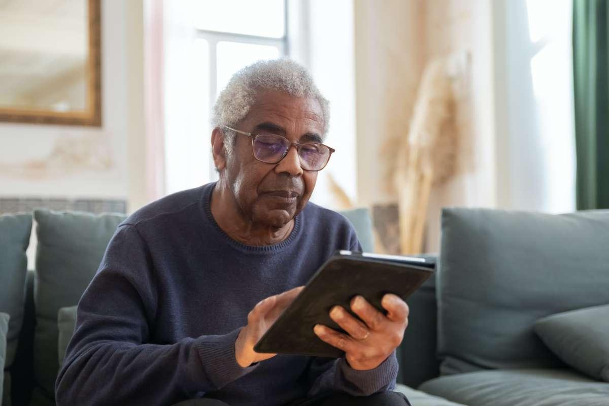 older adult holds Ipad